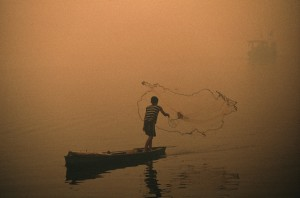 A boy casts his fishing net amidst smog from forest fires.