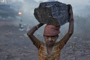 A young boy carries a chunk of coal into the mining camp where he lives.